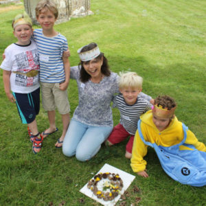 Sally and the boys with their completed nature crown made with fir cones and flowers